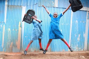 these school children seem very excited about their solular backpacks